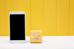 Cellphone and small gift box over yellow wood Royalty Free Stock Image