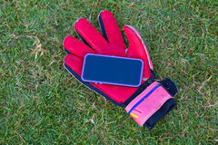 Cellphone on top of a red soccer glove royalty free stock photography