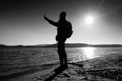 Cellphone van de mensenholding, nemend beeld van de herfstzonsondergang of zonsopgang in schilderachtig overzees landschap stock foto
