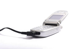 Cellphone on white background. Cellphone with charging cable on white background Royalty Free Stock Photography