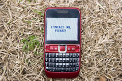 Cellphone in the winter grass lawn. Contact me,pleasewriten in the screen Stock Photo
