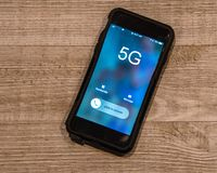 Cellphone on wooden background. The screen says 5G. stock photo