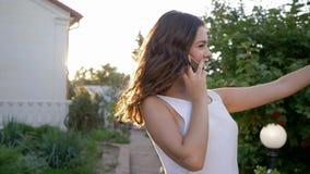 Cellulaire mededeling, aantrekkelijke jonge vrouw die op telefoonclose-up spreken in heldere zonnig stock videobeelden