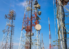 Cellular communication towers on blue sky. Background Royalty Free Stock Photo