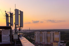 Cellular communications tower on a background of the city and a beautiful sunset in summer Stock Photos
