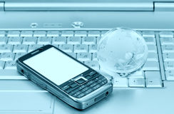 Cellular and glass globe on notebook Royalty Free Stock Image