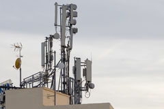 Cellular phone antennas on a building roof. Royalty Free Stock Photos
