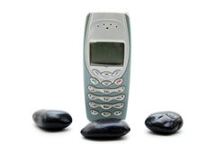 Cellular phone with black stones Royalty Free Stock Photography