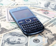 Cellular phone on dollars Royalty Free Stock Photo