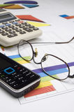 Cellular Phone, Eyeglasses and Calculator. Cellular Phone, Eyeglasses, Calculator and business graphs Stock Images