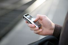 Cellular Phone in Hand. Hand holding a cellular modern phone with blurred backround Royalty Free Stock Image