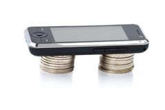 Cellular phone lays on stacks of coins Royalty Free Stock Images
