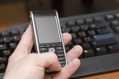 Cellular phone in mans hand. Modern smartphone in hand of a caucasian man, keyboard background Royalty Free Stock Image