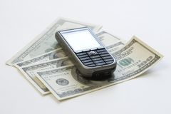 Cellular phone & money. (US dollars) on a light gray background Royalty Free Stock Image