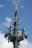 Cellular phone network mast. A cellular phone network mast with different kind of antennas photographed in the summer sun with blue sky and clouds in the stock photography