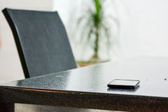 Cellular phone on the table. Near a modern chair Stock Image