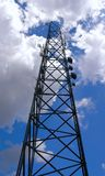 Cellular tower reaching the clouds. Black cellular tower against the sky and the clouds Stock Photo