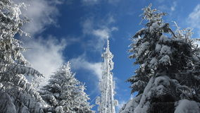 Cellular tower in snow on a blue sky background with clouds passing by stock video footage