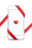 Cellulare bianco con cuore rosso e nastro su bianco Fotografia Stock