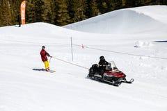 Cellulare della neve che rimorchia uno sciatore nell'alta sierra La Mecca degli sport invernali giugno e di Mammoth Mountain, di  Fotografie Stock Libere da Diritti