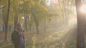 Cellulare di conversazione barbuto bello del telefono del giovane nel parco di autunno stock footage