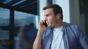 Cellulare di conversazione dell'uomo di affari vicino alla finestra Uomo nervoso che spiega la sua posizione archivi video