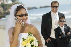 Cellulare di risposta della sposa alla spiaggia Immagini Stock