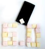 Cellulare e caramella gommosa e molle con sei numeri zero Fotografia Stock