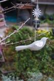Cellulare grigio dell'uccello decorato sui rami nel giardino fotografia stock