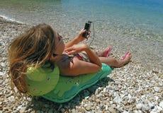 Cellulare, la ragazza che si trova sui giocattoli della spiaggia ascolta musica Fotografia Stock Libera da Diritti