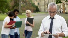 Cellulare maschio senior app sulla compressa vicino all'istituto universitario, istruzione superiore di scorrimento di decano video d archivio