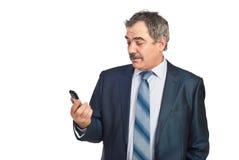 Cellulare maturo sorpreso della holding dell'uomo d'affari Fotografia Stock