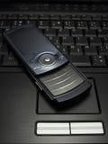 Cellulare nero sul computer portatile Immagine Stock Libera da Diritti
