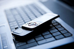 Cellulare su un computer portatile Fotografie Stock Libere da Diritti
