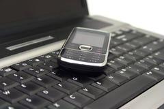 Cellulare su una tastiera del taccuino Immagine Stock