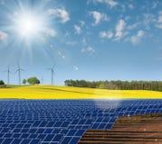 Cellule di energia solare, giacimento del seme di ravizzone e mulini a vento Fotografia Stock