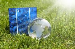 Cellule a energia solare con il globo di glas e la casa miniatura in erba verde fotografia stock libera da diritti