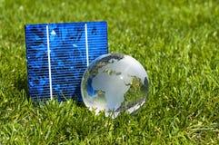 Cellules ? ?nergie solaire avec le globe de glas et la maison miniature dans l'herbe verte photo stock