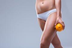 Cellulitis. Female hips with orange on white background stock photography