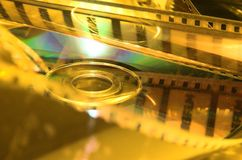 Celluloid with DVD in yellow. Movie film with DVD in mirror Stock Photos