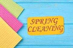 Cellulose sponge cloths on wooden table. Kitchen cleaning napkin and paper card with text spring cleaning stock photography