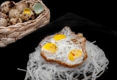Celofán con los huevos de codornices revueltos con los huevos en una cesta en el fondo, en un fondo negro Imagen de archivo libre de regalías