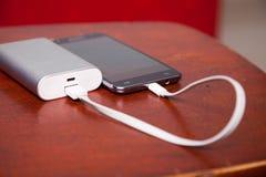 Celtelefoon die met Machtsbank belasten Stock Fotografie
