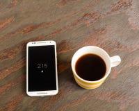 Celtelefoon en koffiekop stock fotografie