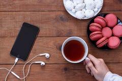 Celtelefoon met hoofdtelefoons, schuimgebakje, makarons en een Kop thee op houten achtergrond stock afbeelding
