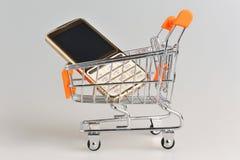 Celtelefoon in supermarkthandkar op grijze achtergrond Stock Fotografie