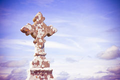 Celtic carved stone cross against a sky background - toned image Stock Image