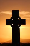 Celtic cross. Silhouetted against an orange sunset royalty free stock photos