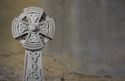 Celtic cross. Weathered celtic cross angainst a grey background stock photo