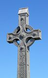 Celtic cross on a blue sky. An old celtic cross in a traditional graveyard stock photo